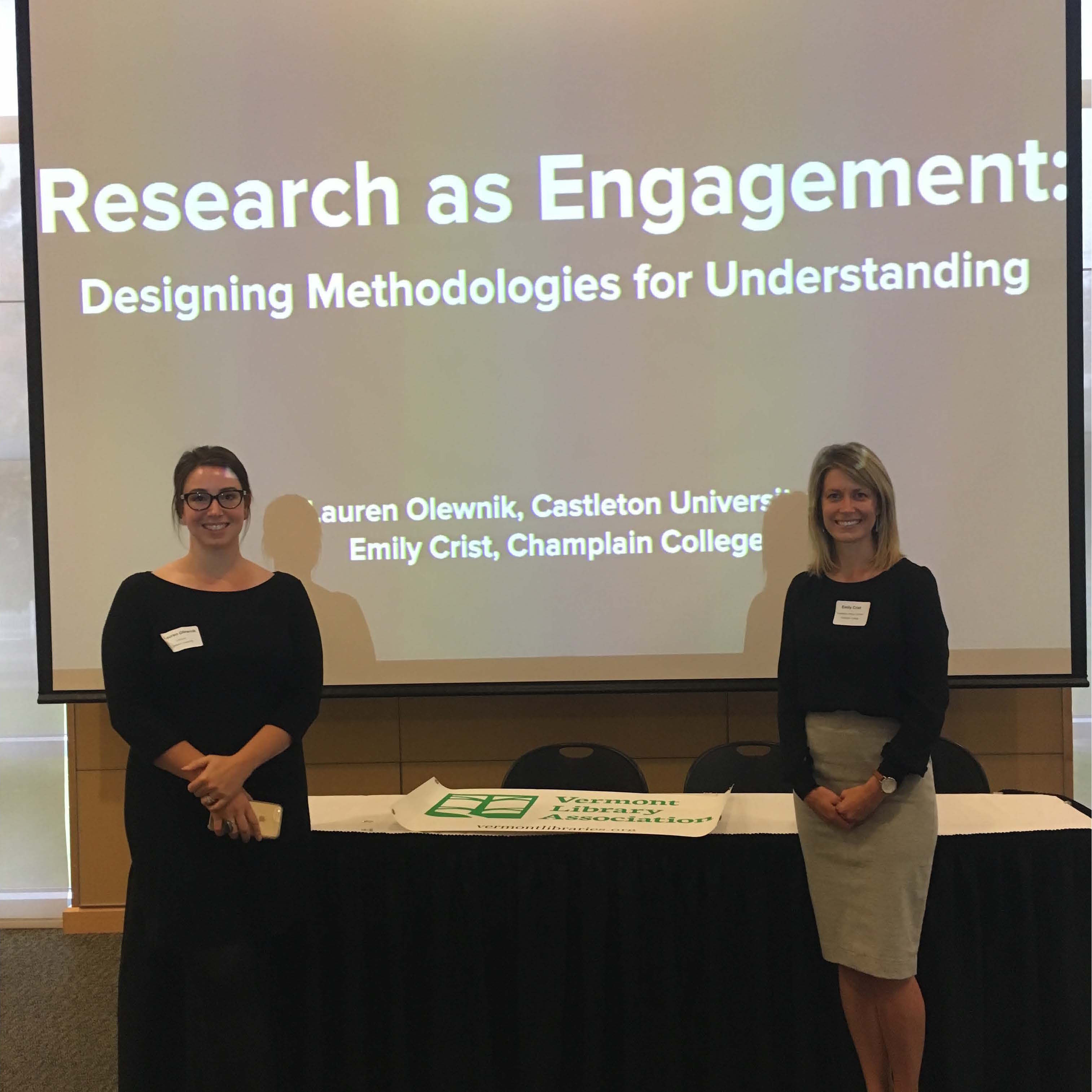 Lauren Olewnik and Emily Crist stand in front of their presentation on Research as Engagement